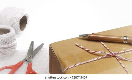 Simple brown postal box lying among other tools and materials used for packing in white background - Shutterstock ID 728745409