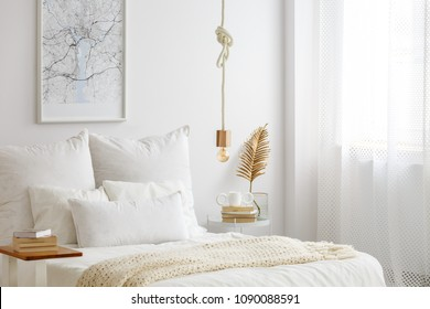 Simple bulb lamp on a rope hanging above bed with white bedclothes, books and gold fern leaf on an end table in white bedroom interior