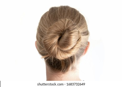 Simple bun hairstyle modeled by young white woman seen from behind close up shot isolated on white 2020
