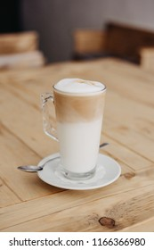 Simple cafe latte made with fresh non-pasteurized milk and a shot of espresso. Coffee on wooden table.