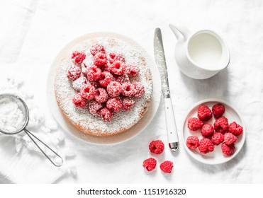Simple cake with powdered sugar and fresh raspberries on a light background. Summer berry dessert. Flat lay