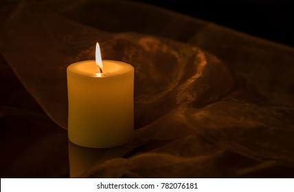 Simple candlelight on a table surrounded by a fine cloth.