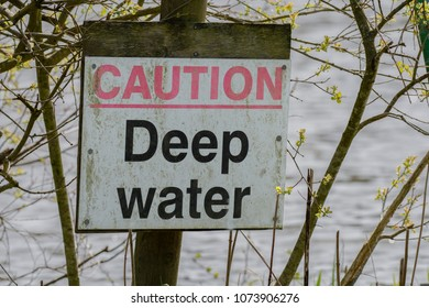 A simple caution sign located by the edge of a pool warning of deep water