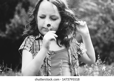 Simple childhood lifestyle concept in nature shows young girl smelling flower in black and white.