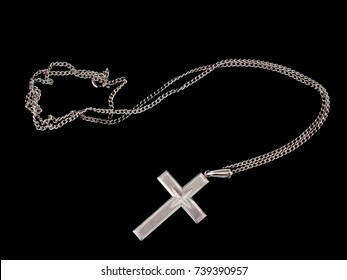 Simple Christian silver cross and chain isolated on black. Religious, faith symbol.