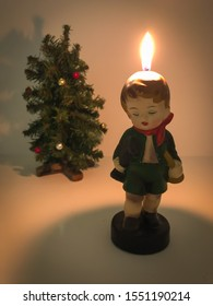 A simple Christmas display of a lighted candle that resembles a vintage figurine of a little boy with a miniature Christmas tree in the background