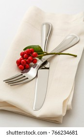 Simple, classic Christmas holiday table setting place setting with high quality silverware fork and knife on white linen napkin. Red holly berries natural decoration. Selective focus on tines of fork.