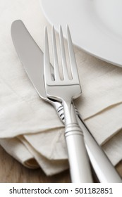 Simple, classic table setting place setting with fork and knife on white linen napkin and white china plate. Selective focus on tines of fork.