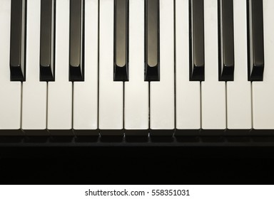 Simple and clean piano keys, one octave, music closeup, space for text on black background