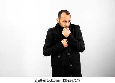 Simple and clean portrait of middle-aged man wearing his black raincoat to hide his face.