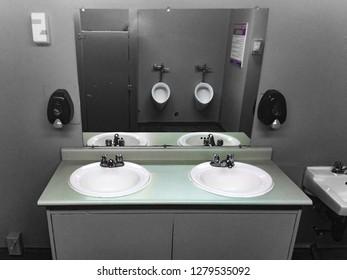 Sencillo pero limpio cuarto de baño para hombres, lavabos y espejos con reflejo de orina, gris de color descolorido