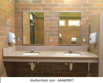 Simple clean public washroom with sinks and mirrors on raw brick wall