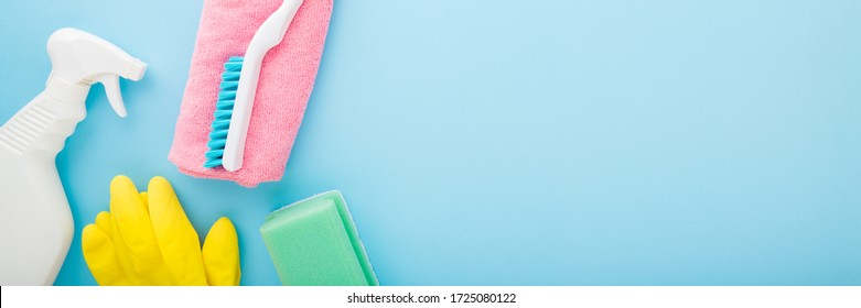 Simple cleaning set for different surfaces in kitchen, bathroom and other rooms. Spring regular cleanup. Light pastel blue background. Closeup. Top view.  Wide banner. Empty place for text or logo.