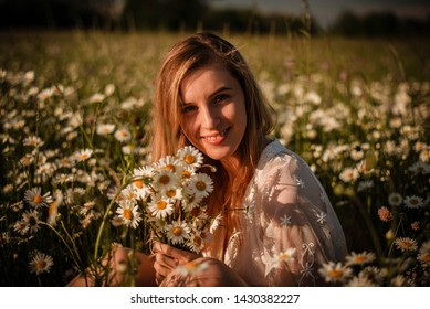 Simple close up portrait of young laughing woman sitting in a daisy meadow wearing white lace playsuit and holding bunch of daisies.