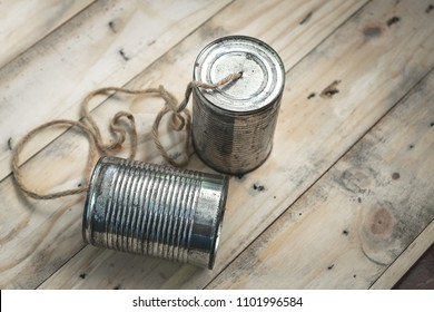 Simple Communication Device Made of Old Tin Can on Wood Background.