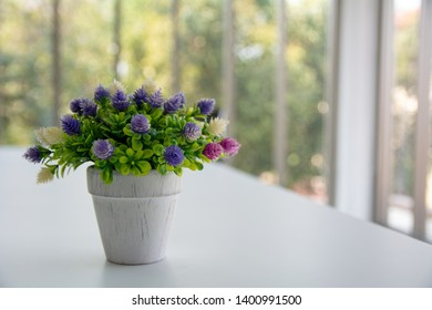 Simple composition with a bouquet of artificial flowers in a glass pot decorated. Rustic handmade decor elements. Romantic style. Vintage design. Violet, green and pink colo