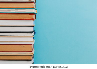 A simple composition of many hardback books, raw books on a wooden table and a bright blue background. back to school. Education.