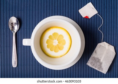 simple composition with tea cup empty but with slice of lemon, saucer and spoon, filter bag of tesu blue striped background