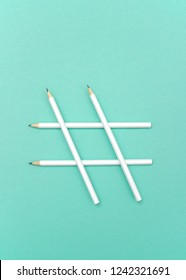 Simple composition of white pencils in sign of hashtag on blue background