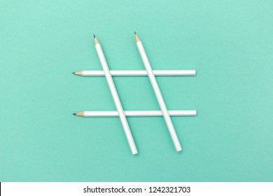 Simple composition of white pencils in sign of hashtag on mint background
