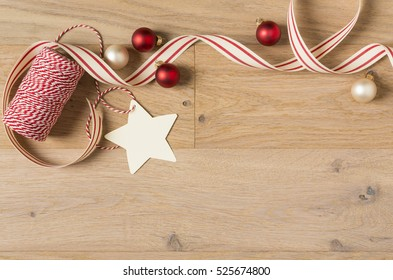 Simple, country style Christmas gift wrapping supplies. Ribbons, baker's twine, ornaments, decorations and blank gift tag on rustic wood horizontal background.