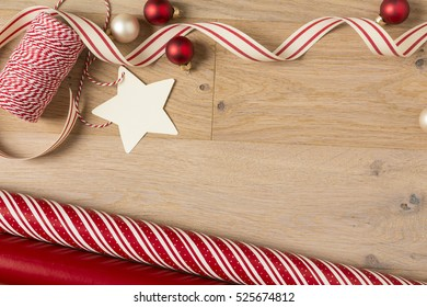 Simple, country style Christmas gift wrapping supplies. Ribbons, baker's twine, wrapping paper, ornaments, decorations and blank gift tag on rustic wood horizontal background.