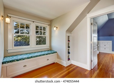 Simple cozy sitting room in the attic with hardwood floor, window seat with drawers and Shelf inserts for books installed into wall. Northwest, USA