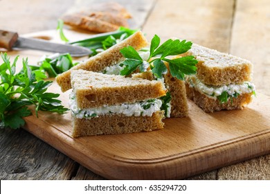 Simple cream cheese sandwiches with parsley and green onion on a table. Delicious healthy homemade snack.