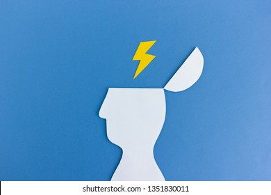 Simple cutout of paper head silhouette with opened mind and yellow thunder striking in it