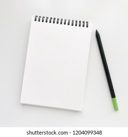 Simple desk mockup with a white spring notebook and a black pencil, top view.