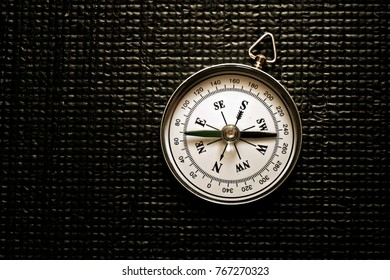 A simple dry magnetic portable compass on a plastic textured black background