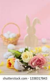 Simple easter decoration with eggs,feathers,  bunny toy and spring flowers.