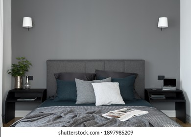Simple and elegant bedroom with gray wall and comfortable bed with gray, upholstered headboard and two, black bedside tables with decorations