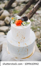Simple elegant modern two tiered white wedding cake decorated with rose flower, a feather and leaves