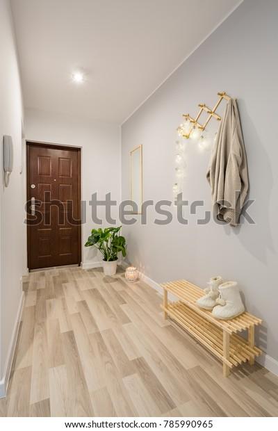 Простой вход с деревянными панелями пола и обувной скамейкой