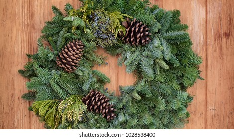 A simple festive evergreen wreath hanging on a wooden door.
