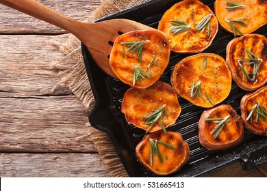 Simple Food: Grilled sweet potatoes with rosemary on the grill pan on the table close-up. horizontal view from above