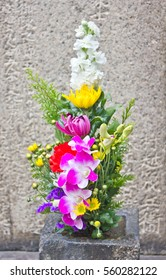 A simple, fresh ikebana flower arrangement marks the grave of an ancient nobleman at the edge of a Buddhist graveyard in Japan.