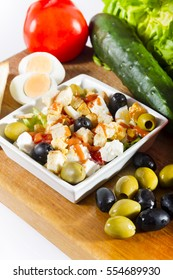 Simple, fresh salad with vegetables and cheese in white bowl on a wooden board next to cucumber, tomato, olives and egg.