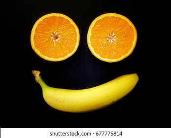 Simple fruit face made of banana and two orange halves on black background