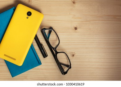 Simple fun and feminine business organizer flatlay - turquoise planner, yellow smartphone, pen and glasses on light wooden surface.