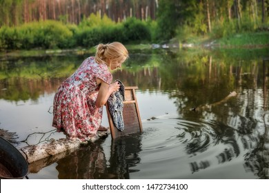 A simple girl washes things on an old washboard in a river in a forest. Retro art photo.