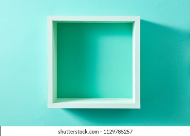 Simple green wood box shelf in the form of a square isolated on a wall of mint color. Product display template