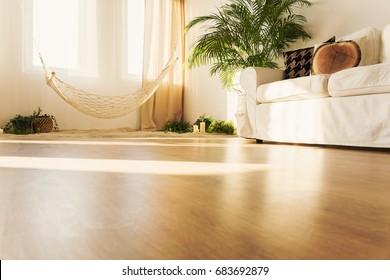 Simple hammock over sand and cozy sofa in elegant bright apartment