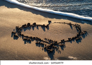 A simple heart shape drawn in the sand with an oncoming wave and sea foam.