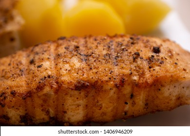 Simple home cooking for bachelors from a marinated grilled filet of haddock and boiled potatoes, yellow boiled potatoes in the background deliberately blurred