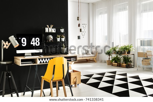 Simple home office desk with computer, yellow chair and handmade lamp in cozy living room with plants