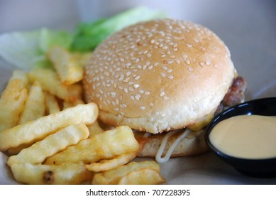 Simple homemade meat burger with french fries, mayonnaise and green leaf vegetable on the side.