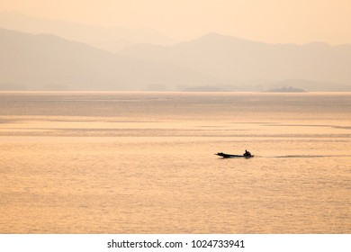 Simple image of a fishing boat in orange light reflecting on the surface. With a mountainous background