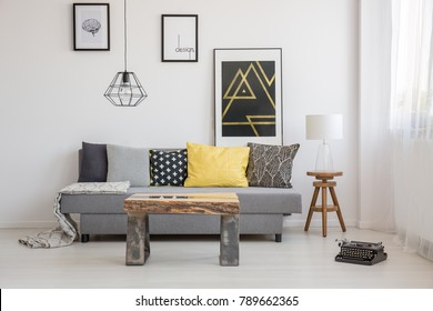 Simple, industrial interior design of living room with wooden table standing in front of a gray sofa with yellow and black cushions